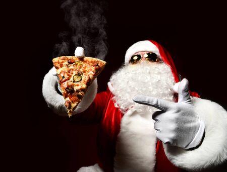 Babbo Natale felice e generoso tiene in mano una fetta fumante di pizza calda che mangia il dito puntato. Concetto di fast food di Capodanno e Buon Natale Archivio Fotografico