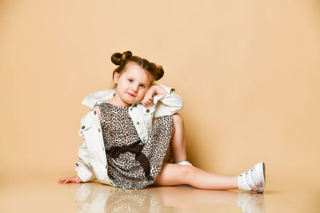 Nice smiling kid girl in leopard print dress and denim jacket is sitting on the floor leaning her head on her hand on background with free copy space