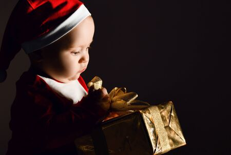 Portrait of infant baby boy toddler in red santa claus costume and christmas cap holding opening his new year gift golden box with ribbon and bow on dark background