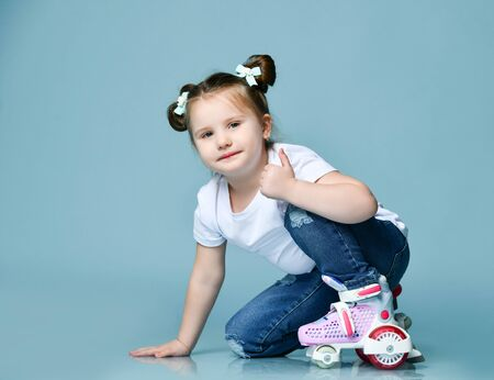Smiling kid girl with funny buns and in t-shirt, blue jeans and roller skates on her feet is sitting, squatting, is on one knee, looking at us, showing thumbs-up gesture, like sign