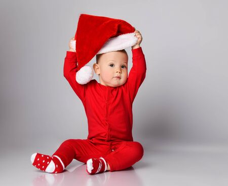 Little boy toddler in red overall and warm christmas socks is putting on playing taking off a santa claus cap with pompon on background with free copy space