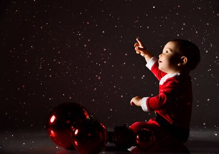 Little toddler boy in santa claus costume is sitting on the floor at big red christmas tree balls decoration looking up pointing his finger at copy space under the snow on dark Zdjęcie Seryjne