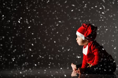 Infant baby boy toddler in red santa claus costume and cap is sitting sideways to us on ice under the snow looking carefully at free copy space ray of light on dark Banco de Imagens