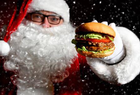 Feliz Papá Noel mantenga sabrosa hamburguesa sándwich de hamburguesa en primer plano de la mano bajo la nieve. Concepto de comida rápida de año nuevo y feliz Navidad Foto de archivo