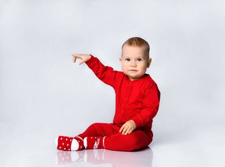 Little toddler boy in red infant bodysuit and socks is sitting on the floor looking is sitting looking at us pointing his finger at side with free text copy space on gray full body