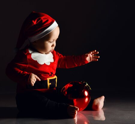 Infant child boy toddler in santa claus costume is occupied playing with a red christmas tree ball fir decoration looking at his reflection holding hand up on dark background