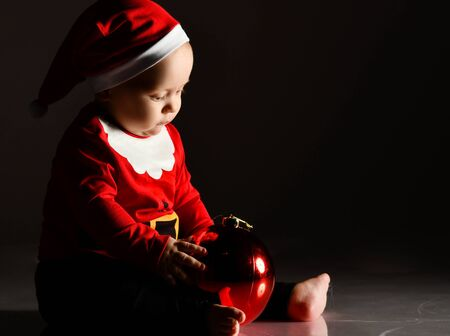 Calm infant child boy toddler in santa claus costume is playing with a red christmas tree ball fir decoration touching reflection on dark background
