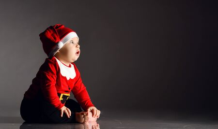 Surprised amazed infant child baby boy toddler is sitting in santa claus costume and cap on ice holding touching his bare feet on dark background looking at free text copy space