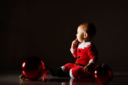 Joyful infant baby boy toddler in santa costume is sitting surrounded by Christmas tree red balls, looking at copy space, reading, holding finger at mouth on dark background