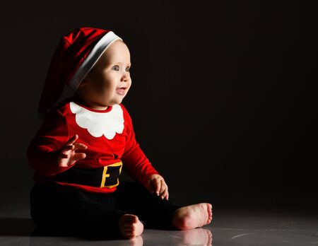 Fascinated infant child baby boy toddler is sitting in santa claus costume and cap on ice is looking at ray of light, christmas show, holding hand up on dark with copy space