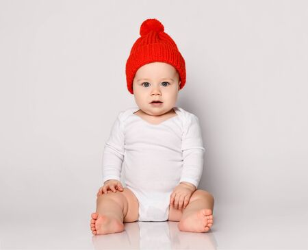 Infant baby boy toddler in white bodysuit and red warm hat with pompon is sitting looking directly straight at camera on white background