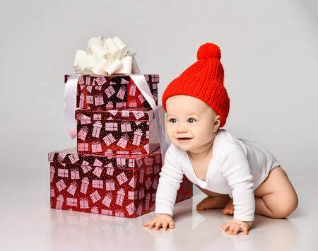 Smiling infant baby boy toddler in white bodysuit and red knitted hat is crawling on all fours at new year christmas gift boxes with ribbon on white background