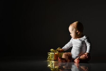 Infant baby boy toddler in white bodysuit is sitting looking at his first new year christmas gift golden box on dark background with free text copy space