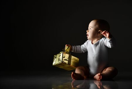 Infant baby boy toddler in white bodysuit is sitting looking at free copy space, holding new year christmas gift golden box by bow, saying, singing on dark background Stock Photo