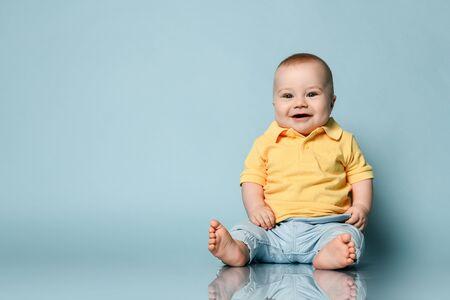 Funny laughing loud barefooted Infant baby boy toddler in yellow shirt and blue jeans is sitting on the floor looking at us on background with free copy space Foto de archivo