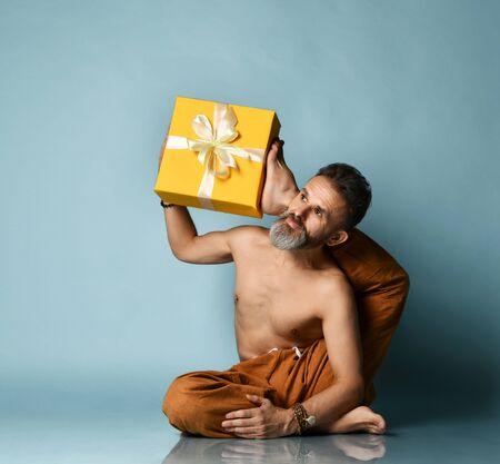Flexible sport mature man does yoga asana stretching exercise holds New Year Christmas yellow gift box Stock Photo