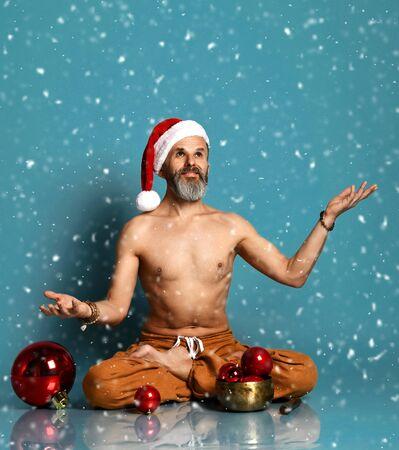 Flexible sport mature man does yoga asana stretching exercise holds red New Year Christmas gift box Stock Photo