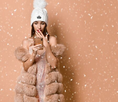 New Year and Xmas concept. Stylish woman in party gown and fur vest is scared upset with news she has got by smartphone, social networks under the snow on beige with copy space. Banco de Imagens