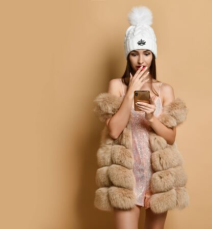 Happy New Year and Merry Christmas. Surprised woman in shimmering party dress, overall, shorts, furs and winter hat is reading message on smartphone covering her mouth with hand