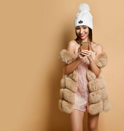 New Year and Christmas. Smiling woman in silver stylish overall suit shorts, furs and winter hat with pompon is reading surprising message on smartphone on beige with copy space