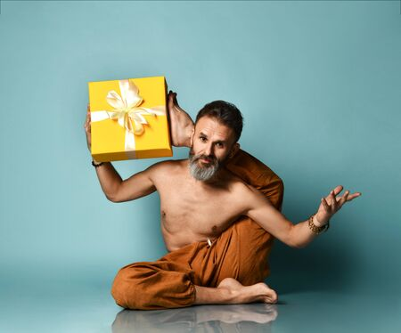 Flexible sport mature man does yoga asana stretching exercise hold yellow gift box with his hand and legs feet.