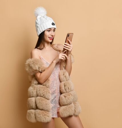 Happy woman in silver dress, fur and winter hat with smartphone, video calling, surprised with prices, sale, online shopping, making orders, got bonus, cashback on beige Banco de Imagens