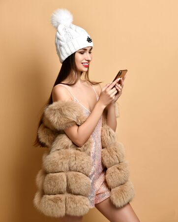 Cheerful rich woman in shimmering strapless dress, furs and white hat with pompon is buying online by her smartphone, typing, reading, surfing, video calling on beige.