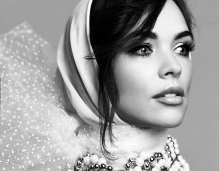 Cheveux bouclés sensuels belle femme mature sourit mystérieusement dans des bagues et des perles de bijoux en perles coûteuses. Image en noir et blanc close up portrait composition Banque d'images