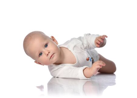Infant child baby boy toddler in white bodysuit white shirt is lying on its side, trying to roll over, held out his hand on white background