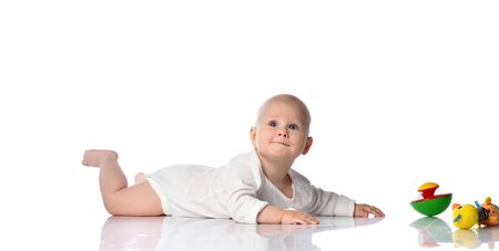Infant child baby boy toddler is lying on his stomach, crawling in white shirt to his colorful toys, looking up with interest, quiet on a white background with cope space above