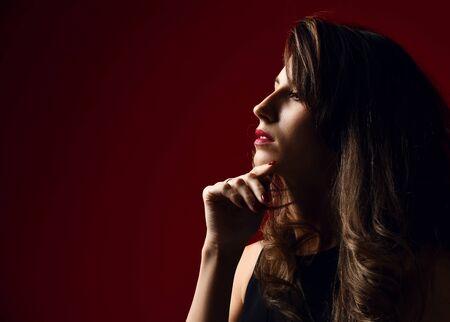 Beautiful woman fashion art studio portrait with windy hair and dark light modern earring posing on red background 版權商用圖片