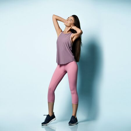Beautiful sport woman in sportswear working out doing stretching sports exercises on light blue background Stock fotó