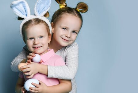 Two small happy girls in cosy home clothing and decorative fur ears standing, hugging and holding white and beige eggs in hands over blue wall background. Family look and celebrating Easter concept
