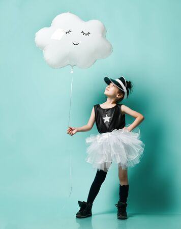 Young asian girl in fashion skirt hold metallic cloud balloon for kids birthday on blue mint background Stock fotó