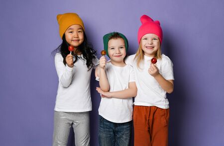 Three funny kids cute smiling friends in white t-shirts and colorful hats stopped their play to eat enjoy lollipops on purple background