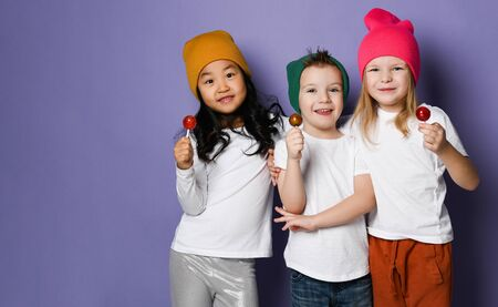 Gang of three cool kids boy and two girls in white t-shirts, colorful hats and pants posing with lollipops hugging together on purple background with free text space Stock Photo
