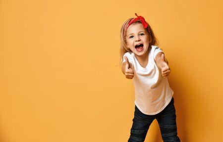 Felice bambino urlante ragazza bionda in una maglietta bianca jeans blu scuro e una benda rossa sulla testa sta mostrando il pollice in alto segno gesto su giallo con spazio di copia