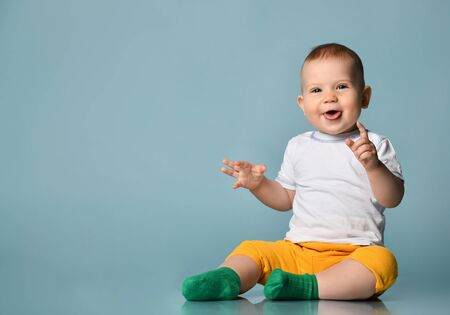 Frolic Infant child baby boy kid in yellow pants and white t-shirt is sitting on the floor stick his tongue out at us on blue background with free text copy space Banque d'images