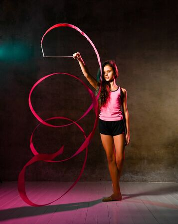Slim athletic girl teenager gymnast with long curly hair is doing rhythmic gymnastic exercises with tape, doing spiral in studio on dark concrete wall background