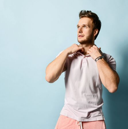 Young smiling handsome man in pink shorts and white polo shirt standing and looking at camera over light blue wall background. Handsome men, stylish outfit and healthy body concept