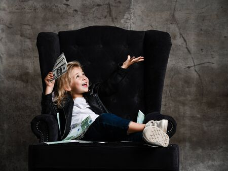 Happy kid girl is sitting in big plush armchair with a wad fan of cash dollars, holding hand up with open palm catching on dark concrete wall background Stock Photo