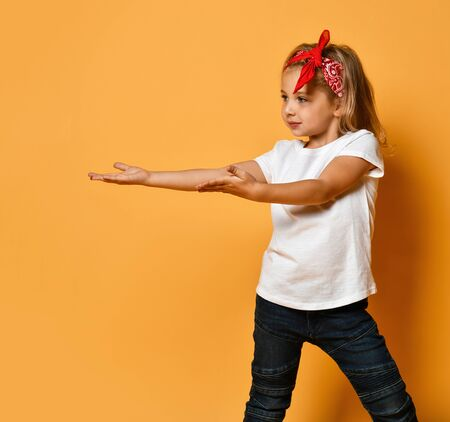 Calm little kid girl in white t-shirt and red headband is standing with her arms outstretched, as if she is holding giving something on her open palms on yellow with copy space