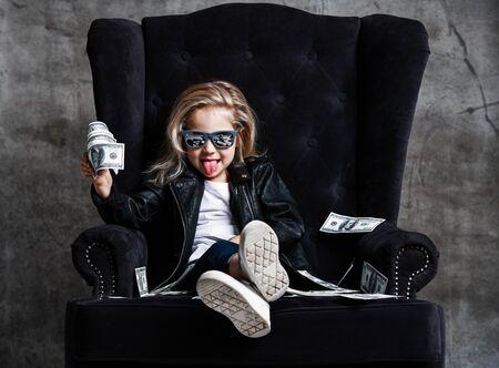 Une fille riche et gambade en veste de cuir et lunettes de soleil est assise dans un grand fauteuil avec une liasse d'argent en dollars qui nous tire la langue en faisant une farce sur fond de mur en béton Banque d'images