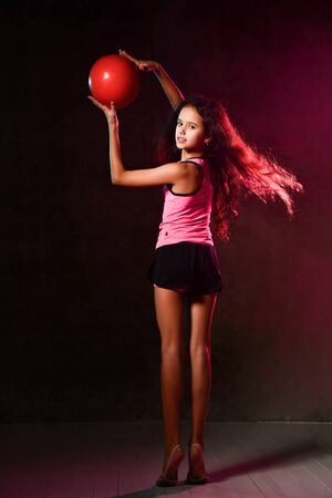 Young athletic girl gymnast with long hair posing with her back to us doing exercises with a red ball holding it up, turning on dark in studio neon light on dark wall background Banco de Imagens