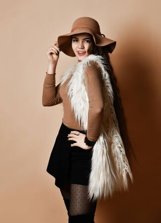 Gorgeous lady with long hair, in brown hat and turtleneck, faux fur sleeveless coat, short black skirt, over the knee boots, bracelet. She is smiling, posing on beige background. Close up, copy space