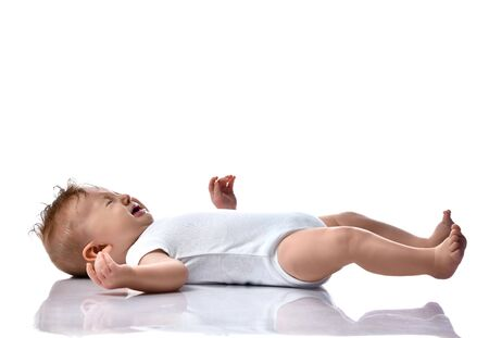 Crying infant child naughty baby boy toddler in white bodysuit is lying on his back on white background with free text copy space Stock Photo