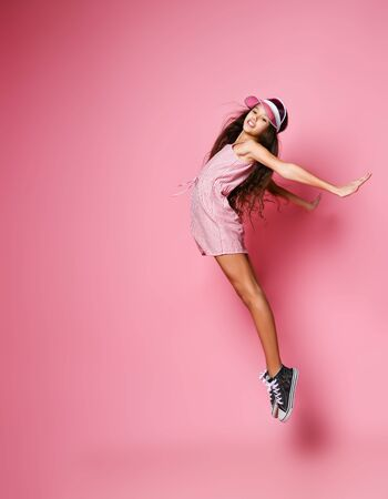 Young slim teenager girl with long windy hair in a stylish cap and pink striped dress is jumping back arched with her arms outstretched on a pink background with free copy space Foto de archivo