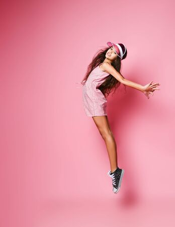 Young athletic teen girl in stylish cap and pink striped dress is jumping pointing her toes back arched with her arms outstretched on a pink background with free copy space