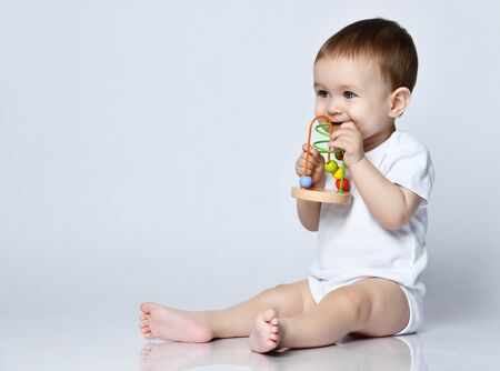 Newborn baby boy toddler in white bodysuit holding playing with a multi-colored developing toy for kids, biting it on a gray background. Preparing for kindergarten Foto de archivo