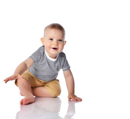 Happy smiling curious infant boy toddler in striped t-shirt and green pants is start crawling going to run fast on all fours on white background with free text copy space